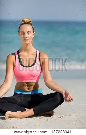Close-up of beautiful woman meditating in lotus position at beach