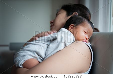 Mother holding her newborn baby beside window. Milk from mother's breast is a natural medicine to baby. Mother day bonding concept with newborn baby nursing.