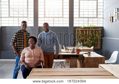 Portrait of three casually dressed young African businesspeople smiling confidently while working together in a large modern office