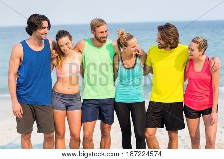Happy friends standing with arm around at beach