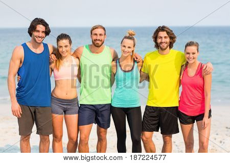 Portrait of happy friends standing with arm around at beach