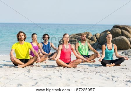 Full length of friends meditating in lotus position on shore at beach