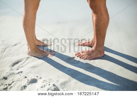 Low section of couple standing on shore at beach