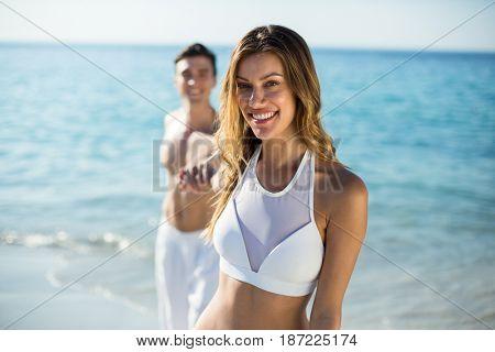 Portrait of happy woman holding boyfriend hand on shore at beach