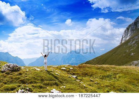 Young woman stands with raised arms up on the nature background in mountain. Slovenia Europe. Mangart Julian Alps National Park Slovenia Europe. Concept of Meditation Relaxation Healthy Life.