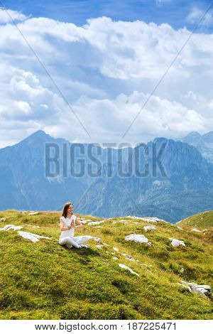 Woman doing yoga and meditating in lotus position on the background of sky and mountains. Mangart Julian Alps National Park Slovenia Europe. Concept of Meditation Relaxation and Healthy Life.