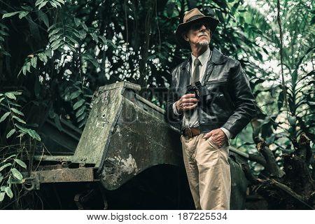 Senior Explorer Standing Next To Car Wreckage In Bush.