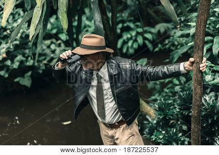 Senior explorer with hat inspecting bush with binoculars.