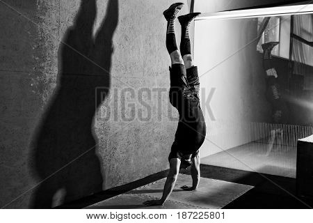 Athlete doing push ups on his hands while standing upside down near red wall. Workout lifestyle concept. Full body length portrait
