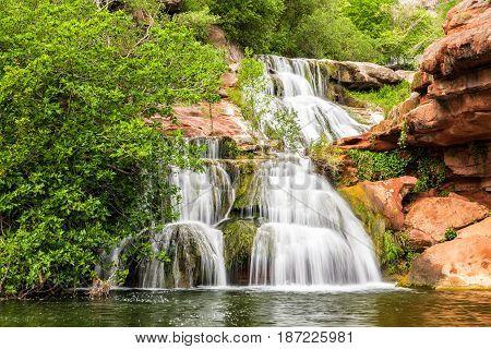 Waterfall cascades on red rocks under Espai Natural Sant Miquel del Fai monastery in Catalonia Spain.