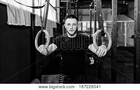 Athlete working out his muscles on rings. Man working out in gym pull ups with gymnastic rings