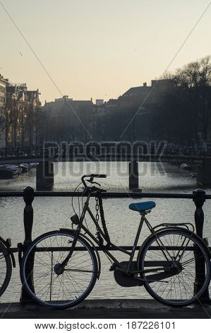 One bike near the canal in Amsterdam in the evening in the dusk