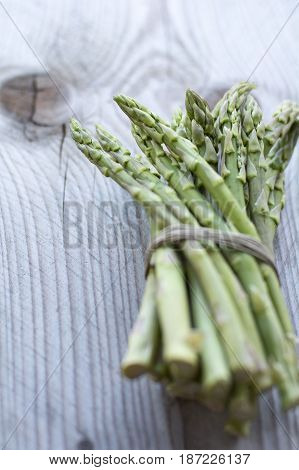 Small bunch of fresh asparagus on the wooden background