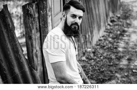 Portrait Of Brutal Stylish Bearded Man With Tattoo In White Tee-shirt Outdoors