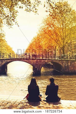 Couple friends or lovers relaxing on embankment of canal and looks at the river and bridges of Amsterdam. Photo toning at retro color. Spring or autumn time in the city. Travel Netherlands Europe.