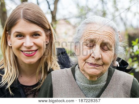 Portrait of an old sick lady with her joyful carer in the park
