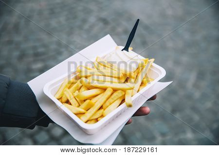 Tourist holds popular street junk food - French Fries with mayonnaise in Holland Amsterdam Netherlands. The Dutch called is patat with mayonnaise or patatje oorlog.