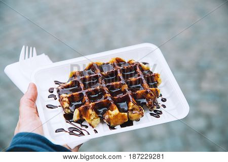 Tourist holds in hand popular street food - Belgium tasty waffle with chocolate sauce on the background of city tourist streets of Bruges Belgium Europe. Traditional Belgian dessert pastry.
