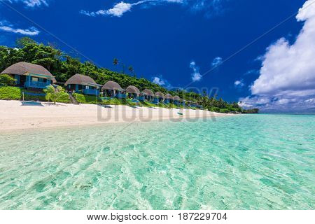 Tropical beach with with coconut palm trees and villas, Polynesia