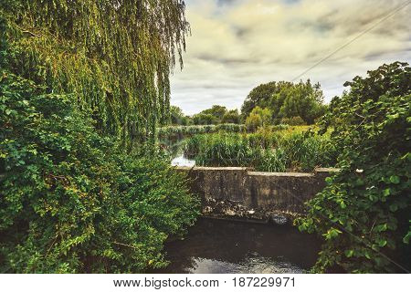 Beautiful English countryside. Stunning landscape over English countryside landscape in Summer sunset. Pond.