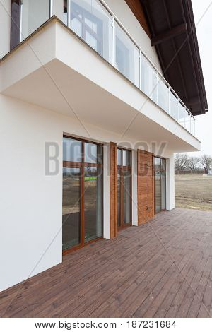 New house with white walls wooden terrace and glass balcon