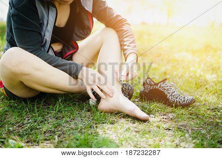 Sporty woman treating her foot ankle. Injury