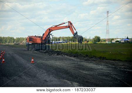 Orange excavator tractor on road repair site.