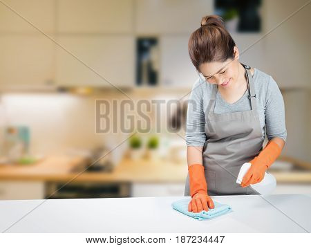asian housewife sweeping on table in kitchen