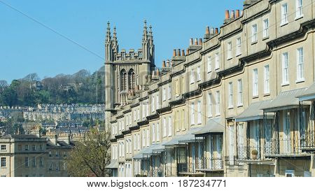 victorian townhouse or terrace in bath city in england united kingdom daytime down hill in a row brick style sunny day / victorian townhouse Bath in england