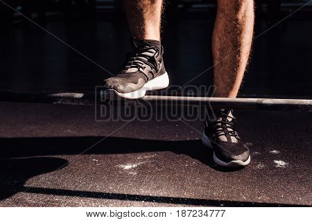 Feet Athlete On The Barbell. Young Athlete Preparing To Lift Weights.