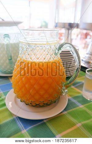 Fresh orange juice in glass jar on table