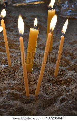 Unas velas encendidas dentro de la arena
