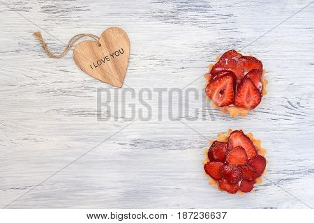 Strawberry cake with a wooden heart on a white wooden table