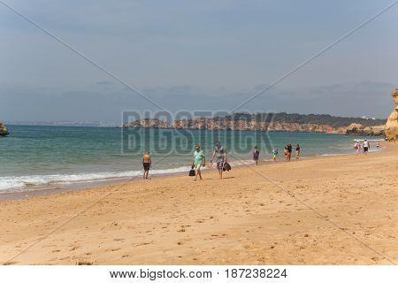 PRAIA DA ROCHA, PORTUGAL - APRIL 25, 2017: People at the famous beach of Praia da Rocha in Portimao. This beach is a part of famous tourist region of Algarve.