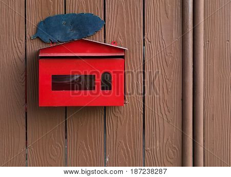 The red steel mailbox on wooden wall