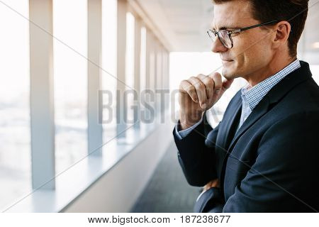 Side view shot of mature businessman standing in office and thinking with hand on chin. Caucasian male entrepreneur in suit and eyeglasses looking pensive.