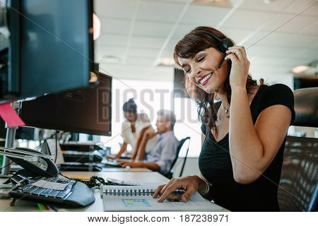 Smiling mature business woman with headset working at her desk and colleagues in background.