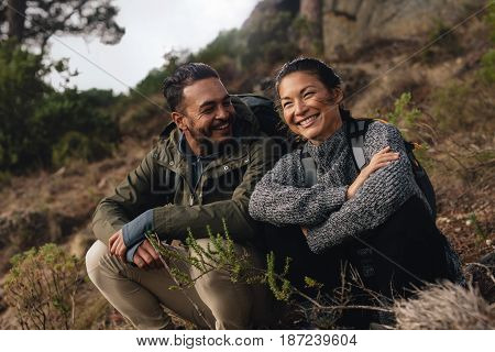 Young couple taking a break on a hike. Happy young man and woman sitting on mountain trail.