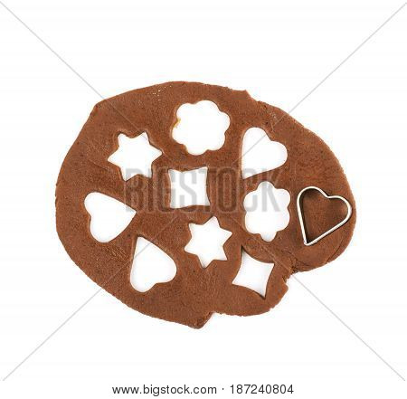 Rolled up thin layer of cookie dough with a heart shaped cookie cutter over it, composition isolated over the white background