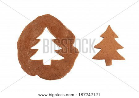 Christmas tree shaped cookie next to a rolled up layer of dough with a cut out, composition isolated over the white background