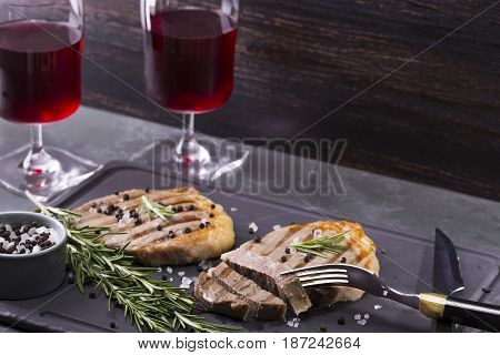 Two steaks on a dark background. Glasses with wine. Place for the inscription.