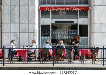 People Dining At Outdoor Tables Of A Dockside Restaurant In Canary Wharf