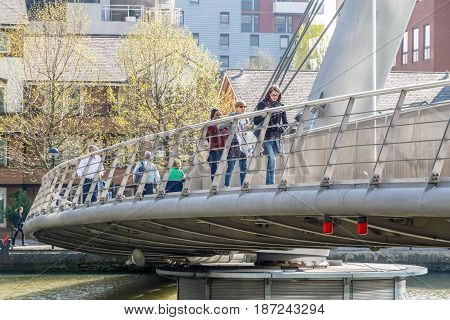 London UK - May 10 2017 - People crossing South Quay footbridge in Canary Wharf