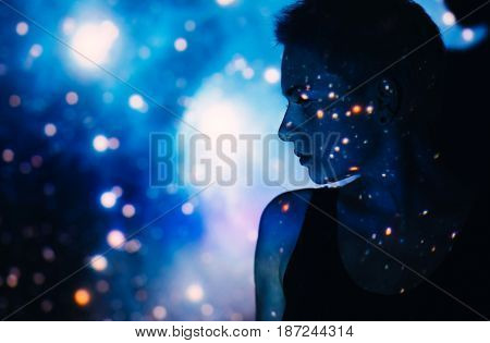 Young beautiful woman lost  in space around stars, photo of a girl with projector