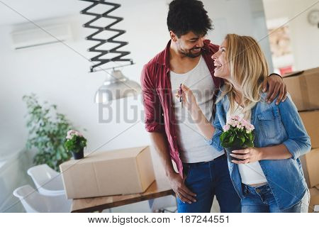 Young happy couple in love moving in new home and unpacking boxes