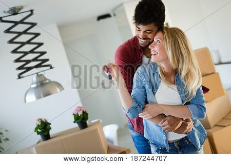 Young married couple with boxes and holding flat keys while moving in