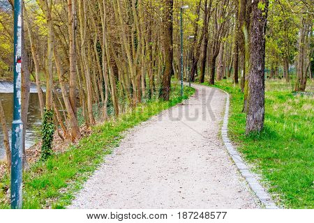 A Hiking trail in a small park next to a river