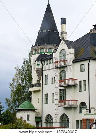 country house with towers against a gray sky