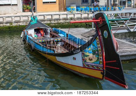 AVEIRO, PORTUGAL - MAY 16, 2017: Traditional boats moliceiro on main city canal. Aveiro, known as Venice of Portugal, also known for its production of salt, which is used for fertilizer in the area.