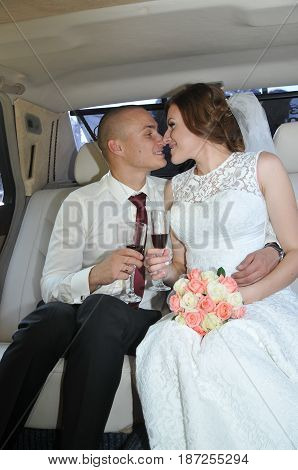 Young bride and groom posing for the camera inside the car